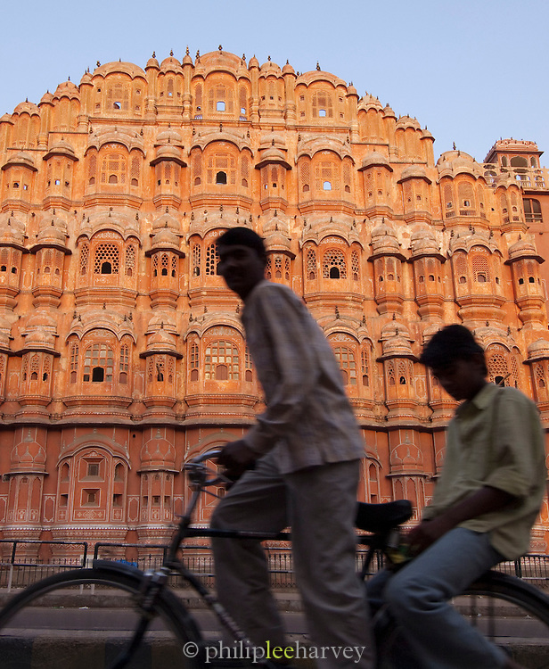 Locals cycling past Hawa Mahal, the Palace of Winds, in Jaipur, India