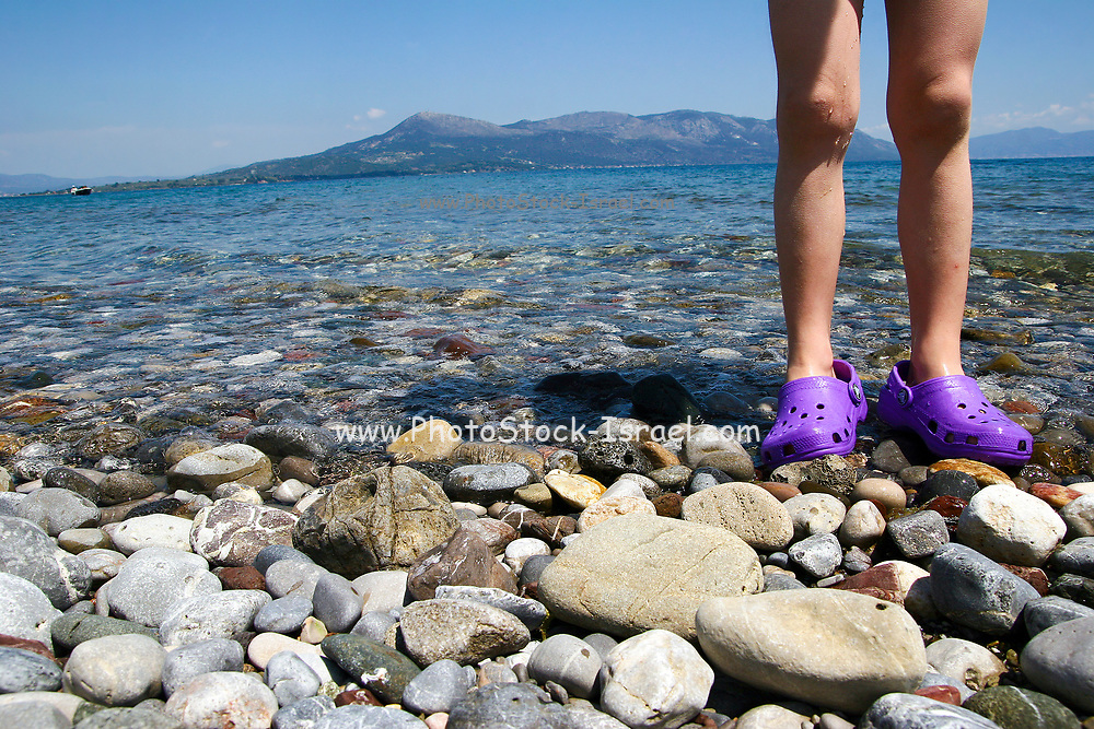 Concept Holiday image of the legs of a young girl standing in the shallow water of the Mediterranean Sea. Photographed in Greece, Thessaly. Model release available