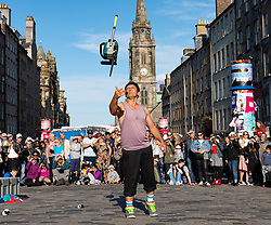 Edinburgh, Scotland, UK. 15 August 2019. Warm sunny weather in Edinburgh brought thousands of tourists onto the Royal Mile to enjoy the many street performers and actors promoting their shows during the Edinburgh Festival Fringe.Performer juggles with chainsaw.  Iain Masterton/Alamy Live News ++ Editorial Use Only ++