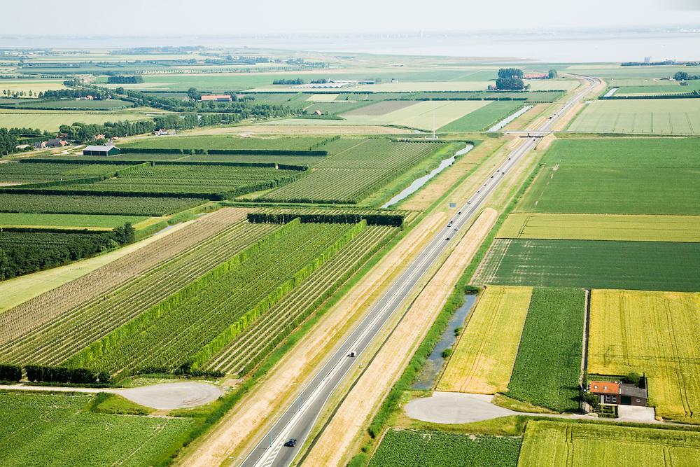 Nederland, Zuid-Beveland, Borssele polder, 04-07-2006; luchtfoto : Westerscheldetunnel, toegangsweg van de tunnel, richting Westerschelde (aan de horizon); aan weerszijden van deze toegangsweg zijn geluidswallen gebouwd om geluidsoverlast te voorkomen; deze geluidsschermen zijn in de vorm van dijken, passend in het omringende landschap (landschappelijke inpassing); de lokale weg die doorsneden wordt heeft keerplaatsen gekregen; landschapsarchitectuur, planologie, verkeer en vervoer, mobiliteit, auto, infrastructuur, milieu; zie ook andere (lucht)foto's van deze lokatie, deevan de serie Panorama Nederland<br />  luchtfoto (toeslag); aerial photo (additional fee required); .foto Siebe Swart / photo Siebe Swart