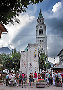 Surprisingly young children climb and rappel (abseil) while harnessed and roped on a practice wall in downtown Cortina d'Ampezzo, Italy, Europe. Afternoon sun rays burst through clouds over the Ampezzo Dolomites. Cortina's parish church, the Basilica dei Santi Filippo e Giacomo, was built 1769-1775, and the new belltower was built 69.50 metres high in 1852-58. The mountain town of Cortina d'Ampezzo (Ladin: Anpëz, German: Hayden, at 1224 meters/4016 feet elevation) is surrounded by the Dolomites (Dolomiti, a part of the Southern Limestone Alps) at the top of Valle del Boite in the Province of Belluno, Veneto region, Italy. This ski resort hosted the 1956 Winter Olympics. UNESCO honored the Dolomites as a natural World Heritage Site in 2009.