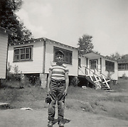 A young boy standing in front of a house