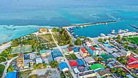 Aerial view of local island Huraa, North Malé Atoll, Maldives, Indian Ocean with tennis court and boats anchoring in the harbour