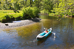 © Licensed to London News Pictures. 12/06/2021. Llanwrtyd Wells, Powys, Wales, UK. A young boy paddles an inflatable canoe on the River Irfon near Llanwrtyd Wells in Powys, Wales, UK. Photo credit: Graham M. Lawrence/LNP