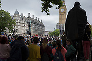 Crowds gather by the statue of Mahatma Gandhi in Parliament Square to hear the last chimes of Big Ben, the giant bell in Elizabeth Tower that rings across London, before its controversial silencing, except for special occasions, by the repair project that is scheduled to be completed by 2021, on 21st August 2017, in London, England.