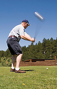 Vertical close-up of golfer swinging club at Valle Escondido Taos Canyon Golf Course