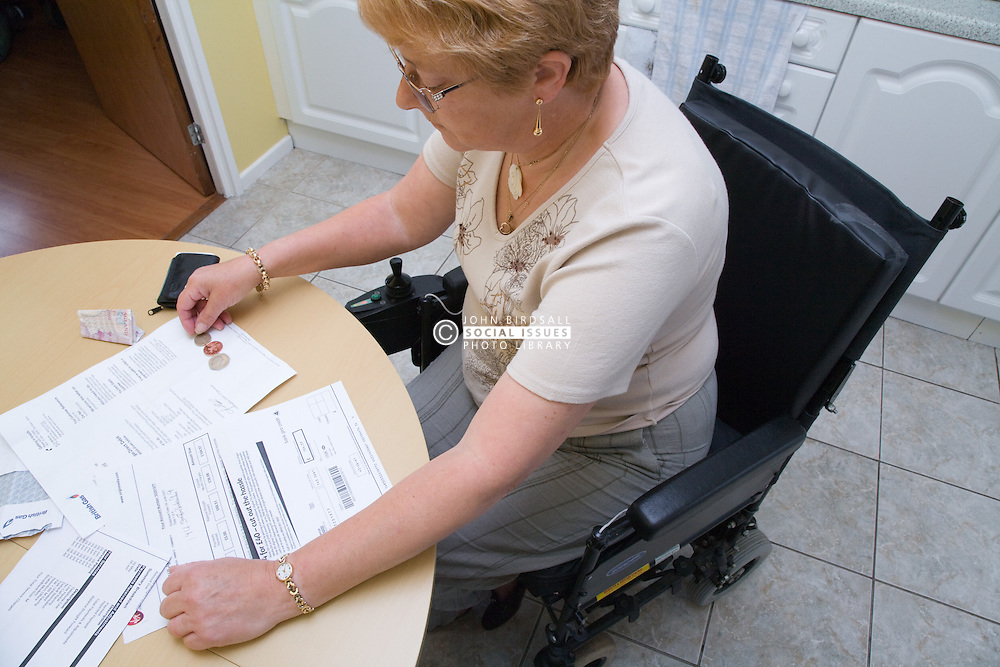 Female wheelchair user sitting at her kitchen table paying some bills,