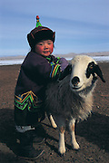 Nomads child with sheep<br /> wearing traditional dress<br /> Gobi Desert<br /> Mongolia