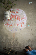 A man asleep beneath a pot plant hung from a wall, Old Delhi, India