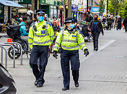 Licensed to London News Pictures. 25/05/2021. London, UK. Community police officers patrol shopping areas in Hounslow west London as Downing Street issues advice to the public to avoid non-essential travel in and out of areas in England affected by the Indian variant including Hounslow in London. On Sunday the government increased surge testing in the area to help combat the new variant. Photo credit: Alex Lentati/LNP