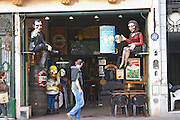 in the San Telmo district around Plaza Dorrego Square, on the square a shop selling flea market things or junk like beer posters and sculptures promoting beer, Homer Simpson, a very busty woman in red and short skirt, a cartoon character, a man in black, a man passing walking Buenos Aires Argentina, South America