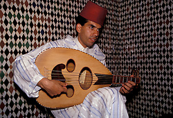 Africa, Morocco, Fes, Musician playing traditional instrument near mosaic tile wall