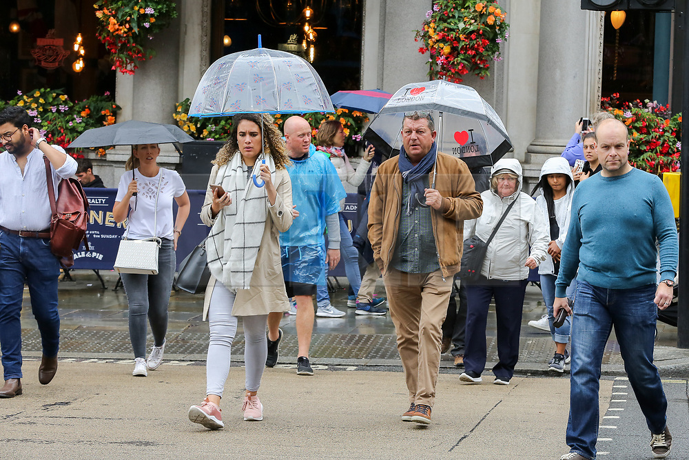 © Licensed to London News Pictures. 16/08/2019. London, UK. Tourists shelter from the rain beneath umbrellas in Westminster. The Met Office has issued a severe weather alert for most of today, as almost a month's worth of rain is expected in many parts of the UK. Photo credit: Dinendra Haria/LNP