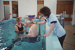 Female physiotherapists lowering elderly patient into hydrotherapy pool,