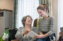Senior women with granddaughter using digital tablet in rest home