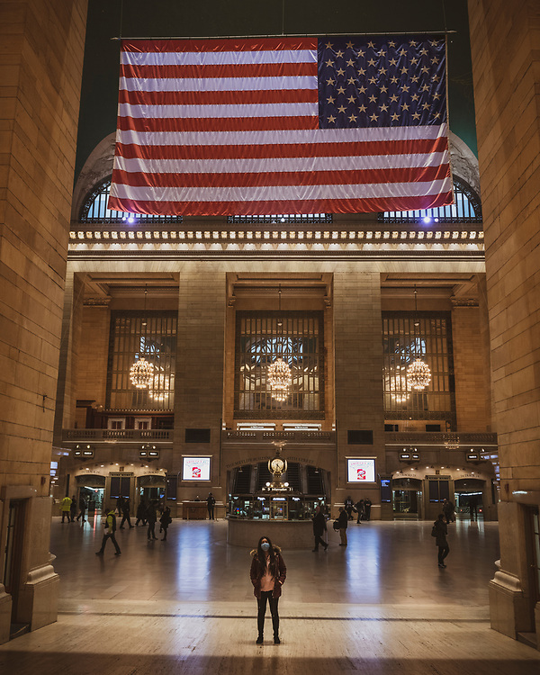 New York City, USA - March 19, 2020: Nathalia, from Venezuela, stands under the American flag in an abnormally quiet Grand Central Station in Midtown Manhattan. She is wearing a face mask in light of the growing cornavirus pandemic. The time is 4:31 pm.