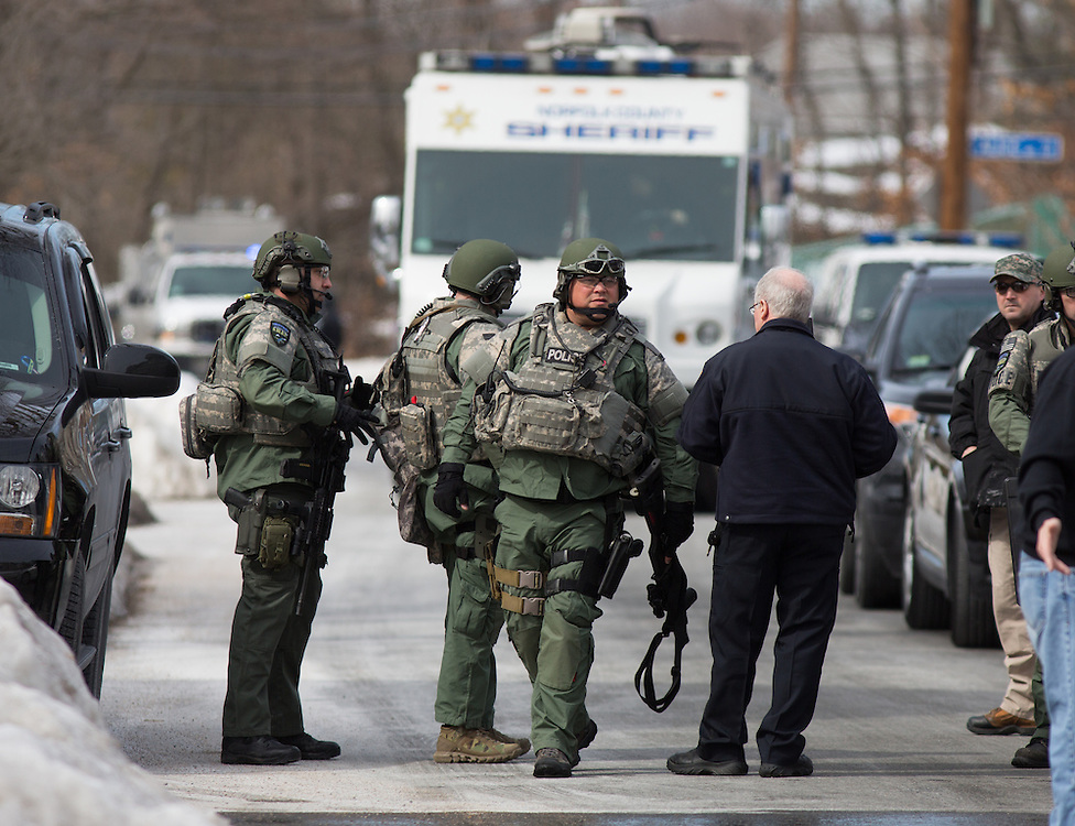Dedham, MA 03/07/2014<br /> Dedham Police and Metro SWAT officers gather on Sherwood St in East Dedham after reports of a man barricaded in a home on Leonard St on Friday afternoon.<br /> Alex Jones / www.alexjonesphoto.com