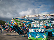 14 AUGUST 2019 - DES MOINES, IOWA: Teenagers on the Hang Glider, a ride on the Midway at the Iowa State Fair. The Iowa State Fair is one of the largest state fairs in the U.S. More than one million people usually visit the fair during its ten day run. The 2019 fair run from August 8 to 18.                PHOTO BY JACK KURTZ