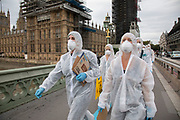 Extinction Rebellion 'crime scene investigators' in white suits and masks walk over Westminster Bridge past the Houses of Parliament with to investigate areas of ecocide in a performance outside the Cabinet Office on 7th September 2020 in London, United Kingdom. The 20 investigators were protesting at the UK government's ecocide along the HS2 route. Extinction Rebellion is a climate change group started in 2018 and has gained a huge following of people committed to peaceful protests. These protests are highlighting that the government is not doing enough to avoid catastrophic climate change and to demand the government take radical action to save the planet.