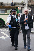 A Metropolitan Police officer arrests an environmental activist from Extinction Rebellion after a vintage bus was used as base to block a road junction to the south of London Bridge on the ninth day of Impossible Rebellion protests on 31st August 2021 in London, United Kingdom. Extinction Rebellion are calling on the UK government to cease all new fossil fuel investment with immediate effect.