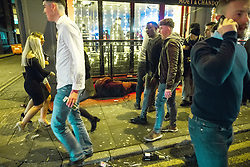 """© Licensed to London News Pictures . 15/12/2017. Manchester, UK. A man , believed to be homeless , sleeps on the pavement in front of a club on Peter Street , as revellers walk around him . Revellers out in Manchester City Centre overnight during """" Mad Friday """" , named for historically being one of the busiest nights of the year for the emergency services in the UK . Photo credit: Joel Goodman/LNP"""