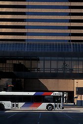Metro bus passing in front of a downtown Houston building