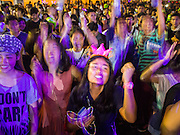 31 DECEMBER 2014 - BANGKOK, THAILAND: A woman dances at the New Year's party in Rathaprasong. Hundreds of thousands of people pack into the Ratchaprasong Intersection in Bangkok for the city's annual New Year's Eve countdown. Many Thais go the Erawan Shrine and Wat Pathum Wanaram near the intersection to pray and make merit before going to their New Year's parties.    PHOTO BY JACK KURTZ