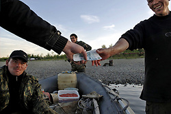 Dmitri Noskov and Astashov Aleksei collect caviar from  Shirmanov Nikolai Mikhilovich (27) and Mikhail Mikhailovich (24) both Chukchi from Khailino, and pay them 500 rubles for every 20 kilograms on the river Vyvenka in Khailina, Kmachatka July 24, 2007. They will take it to a caviar processign plant and then ship it to Tilichicki where it will be sold to foreign markets.