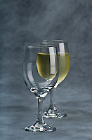 Empty cup of glass with other cup with white wine behind. Gray Background space for copy on top.