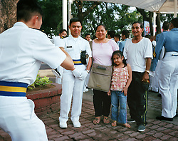 A proud family gets a snapshot taken with their son as seafarers gather for a holiday event in Manila, Philippines on Dec. 2006.  Working at sea is a common profession for OFWs but it has its own drawbacks including prolonged trips where the crews have not been ashore for four months because of increased international security regulations. There are more than 10 million overseas Filipinos worldwide, about 11% of the total population of the Philippines.  Each year, the Philippines sends out more than a million of its nationals to work abroad through its overseas employment program.