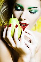 beautiful caucasian woman portrait holding pear studio on yellow background
