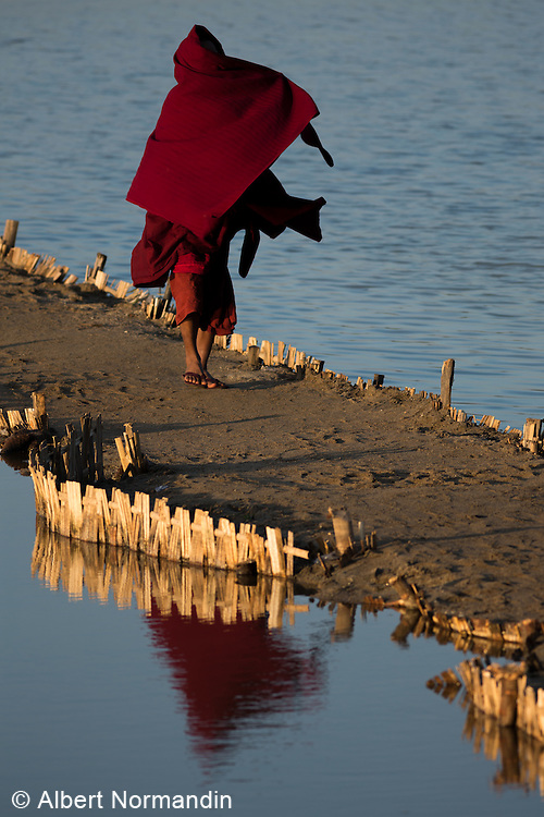 Monk in red robe blowing in the wind, Chindwin River