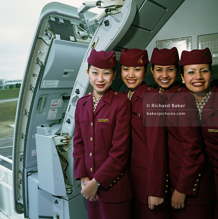 Posing in the open doorway of an Airbus A319CJ Business jet, four female cabin crew members wear the uniforms of Qatar Airways whose airline has made a public relations stop at the Farnborough Air Show to publicise this new model of executive service. Airline stewards and stewardesses are nowadays more commonly referred to as cabin crew or flight attendants. They stand close together with broad grins showing their varied ethnicity. Middle-Eastern airlines generally recruit men and women from western Europe, Asia, Australasia and the Indian sub-continent dependent on routes and aircraft type. Picture from the 'Plane Pictures' project, a celebration of aviation aesthetics and flying culture, 100 years after the Wright brothers first 12 seconds/120 feet powered flight at Kitty Hawk,1903..