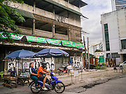 "07 OCTOBER 2012 - BANGKOK, THAILAND:  A motorcycle taxi takes a fare past an empty building in the process of being demolished in Washington Square in Bangkok. Washington Square was a notorious Bangkok ""entertainment district"" at the end of Soi 22 on Sukhumvit Road with several bars, massage parlors and restaurants that appealed primarily to older western male retirees, called ""sexpats"" by Bangkok residents. It was established during the Vietnam War when American servicemen on Rest and Recreation (R&R) leave from Vietnam visited Bangkok for its inexpensive nightlife and liquor. Its reputation was solidified after the war, when American military and intelligence agency retirees settled in Bangkok. Bars in Washington Square have been closing as their leases expire and the area was razed over the summer. The owners of the land are expected to redevelop it into a high rise condominium, office tower or hotel.    PHOTO BY JACK KURTZ"
