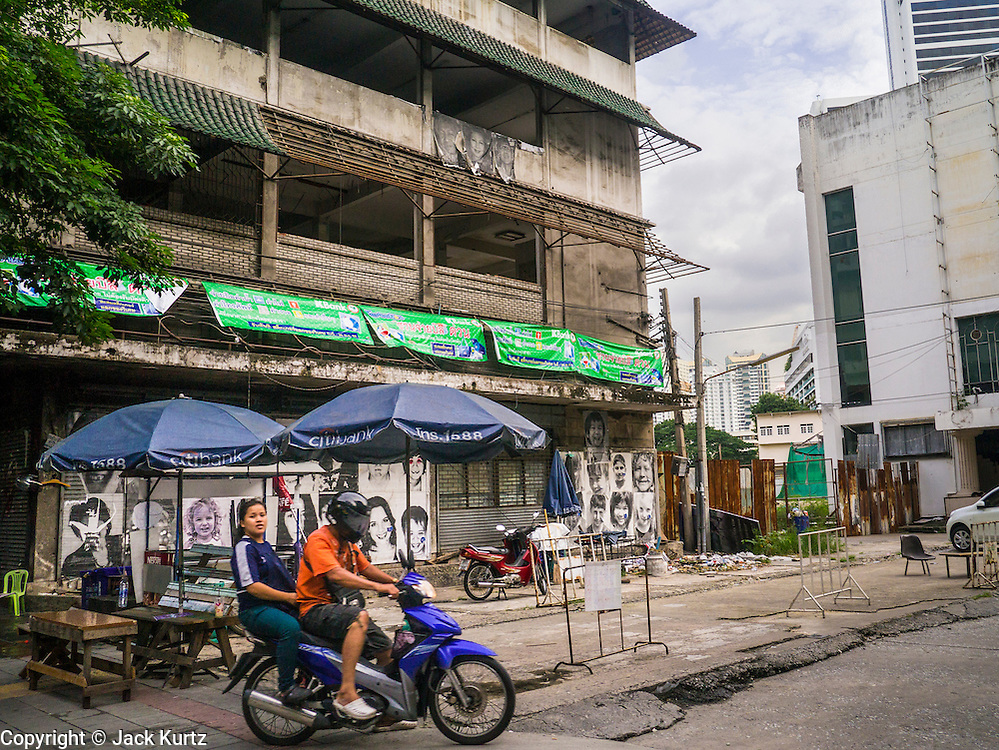 """07 OCTOBER 2012 - BANGKOK, THAILAND:  A motorcycle taxi takes a fare past an empty building in the process of being demolished in Washington Square in Bangkok. Washington Square was a notorious Bangkok """"entertainment district"""" at the end of Soi 22 on Sukhumvit Road with several bars, massage parlors and restaurants that appealed primarily to older western male retirees, called """"sexpats"""" by Bangkok residents. It was established during the Vietnam War when American servicemen on Rest and Recreation (R&R) leave from Vietnam visited Bangkok for its inexpensive nightlife and liquor. Its reputation was solidified after the war, when American military and intelligence agency retirees settled in Bangkok. Bars in Washington Square have been closing as their leases expire and the area was razed over the summer. The owners of the land are expected to redevelop it into a high rise condominium, office tower or hotel.    PHOTO BY JACK KURTZ"""