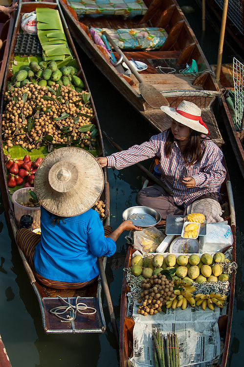 Women selling fruit from their canoes at the Floating Market in Damnoensaduak, Thailand. They are villagers selling their wares from canoes or row boats in the canals west of Bangkok.