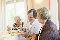 Caregiver watching photos with senior women at rest home, Bavaria, Germany