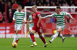 Aberdeen's Ross McCrorie (centre) and Celtic's David Turnbull battle for the ball during the cinch Premiership match at Pittodrie Stadium, Aberdeen. Picture date: Sunday October 3, 2021.