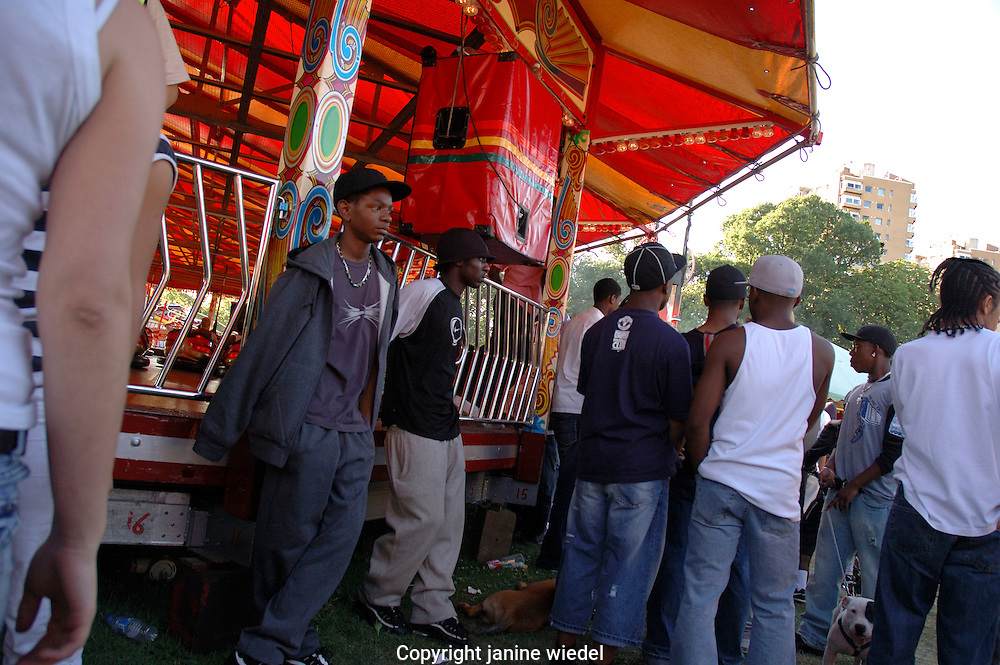 Group of youth hanging around Fun Fair at Lambeth Country Fair in Brockwell Park Brixton South London.
