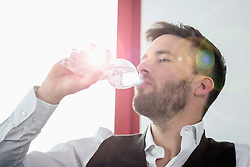 Young businessman thirsty drinking mineral water
