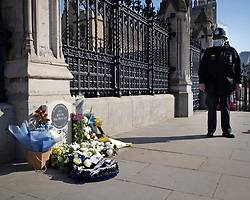© Licensed to London News Pictures. 22/03/2021. London, UK. A police officer stands next to the PC Keith Palmer memorial outside the Houses of Parliament. Today marks four years since the Westminster Bridge terror attack and a commemorative plaque is expected to be installed on Westminster Bridge when Coronavirus restrictions are lifted . Photo credit: George Cracknell Wright/LNP