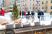 People enjoy winter sports by ice skating on the Edgewater Hotel's rink; Madison, Wisconsin, USA. February, 2021.