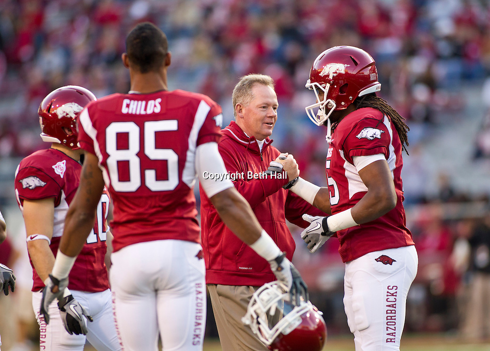 Nov 5, 2011; Fayetteville, AR, USA;  Arkansas Razorback head coach Bobby Petrino, second from right, shakes hands with wide receiver Keante Minor (15) as wide receiver Greg Childs (85) looks on before the start of a game against the South Carolina Gamecocks at Donald W. Reynolds Stadium.  Mandatory Credit: Beth Hall-US PRESSWIRE