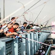 Fishing off Istanbul's historic Galata Bridge spanning the Golden Horn.