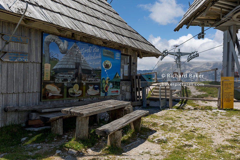 The chairlift station in Velika Planina, on 26th June 2018, in Velika Planina, near Kamnik, Slovenia. Velika Planina is a mountain plateau in the Kamnik–Savinja Alps - a 5.8 square kilometres area 1,500 metres (4,900 feet) above sea level. Otherwise known as The Big Pasture Plateau, Velika Planina is a winter skiing destination and hiking route in summer. The herders' huts became popular in the early 1930s as holiday cabins (known as bajtarstvo) but these were were destroyed by the Germans during WW2 and rebuilt right afterwards by Vlasto Kopac in the summer of 1945.
