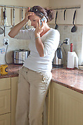 Polish woman age 32 talking on phone in modern kitchen. Zawady Central Poland