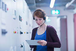 Young female engineer wearing headset and updating control panel using digital tablet in an industrial plant, Freiburg im Breisgau, Baden-Wuerttemberg, Germany