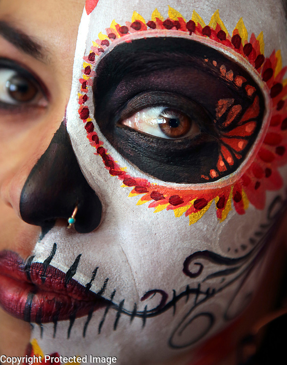 Fine Art painter Evelyn Salguero, who began creating intricate face painted designs for Dia de los Muertos celebrations 8 years ago, practices her craft on her own face as she prepares for the holiday. Dia de los Muertos focuses on gatherings of family and friends to pray for, and remember friends and family members who have died, and help support their spiritual journey. Celebrants of the holiday, which originated in central and southern Mexico, believe that at midnight on October 31, the souls of all deceased children come down from heaven and reunite with their families on November 1. The souls of deceased adults are believed to visit on November 2. Photographed in Santa Cruz, California on September 4, 2018.<br /> Photo by Shmuel Thaler <br /> shmuel_thaler@yahoo.com www.shmuelthaler.com