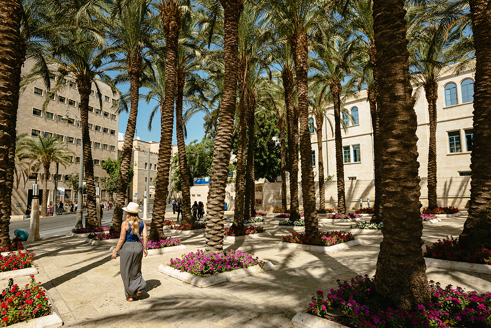 A woman walks past palm trees at Safra Square in Jerusalem