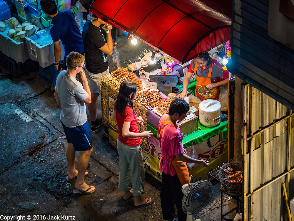 17 JANUARY 2016 - BANGKOK, THAILAND: People buy grilled meats and sausages from a vendor on Sukhumvit Soi 38, one of the most famous street food areas in Bangkok. The food carts and small restaurants along the street have been popular with tourists and Thais alike for more than 40 years. The family that owns the land along the soi recently decided to sell to a condominium developer and not renew the restaurant owners' leases. More than 40 restaurants and food carts will have to close. Most of the restaurants on the street closed during the summer of 2015. The remaining restaurants are supposed to close by the end of this week.           PHOTO BY JACK KURTZ